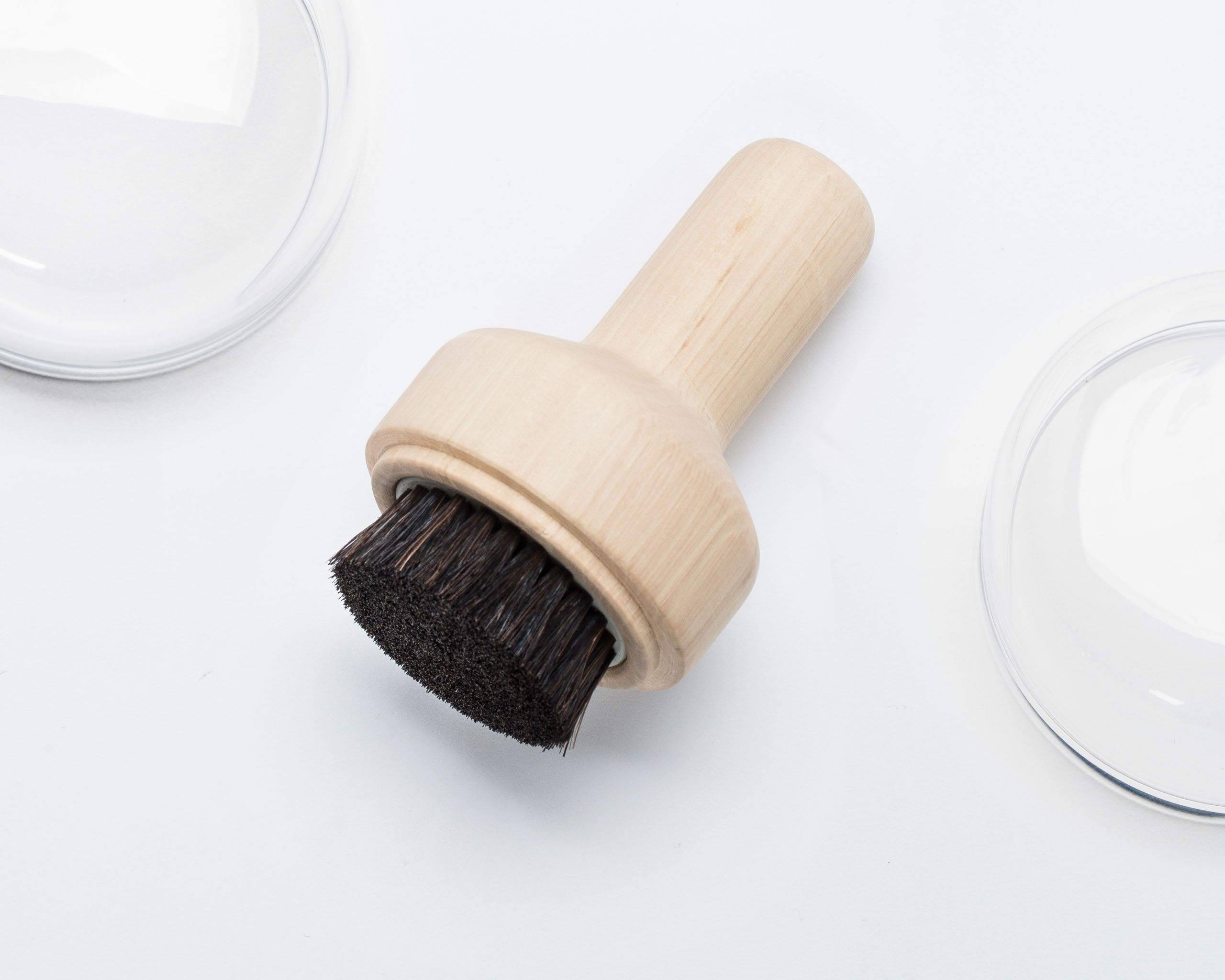 A shoe brush made of wood and natural bristles with an extended handle.