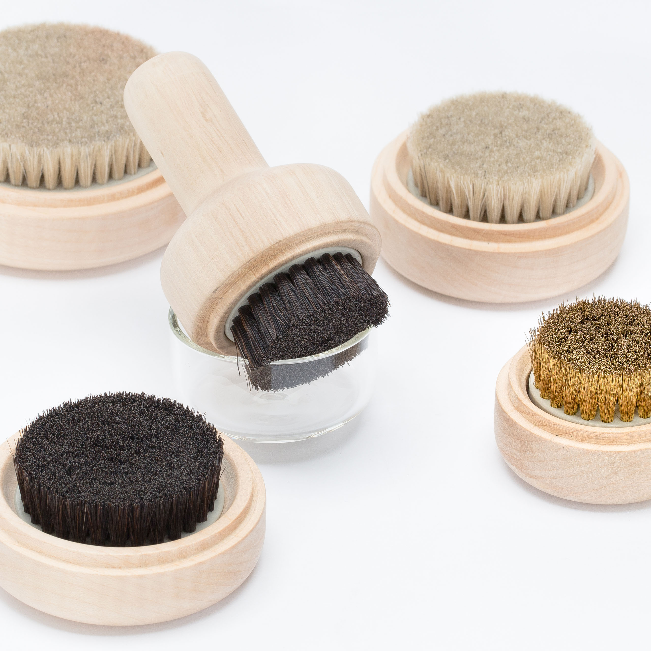 Five clothing brushes are arranged on a white backdrop.
