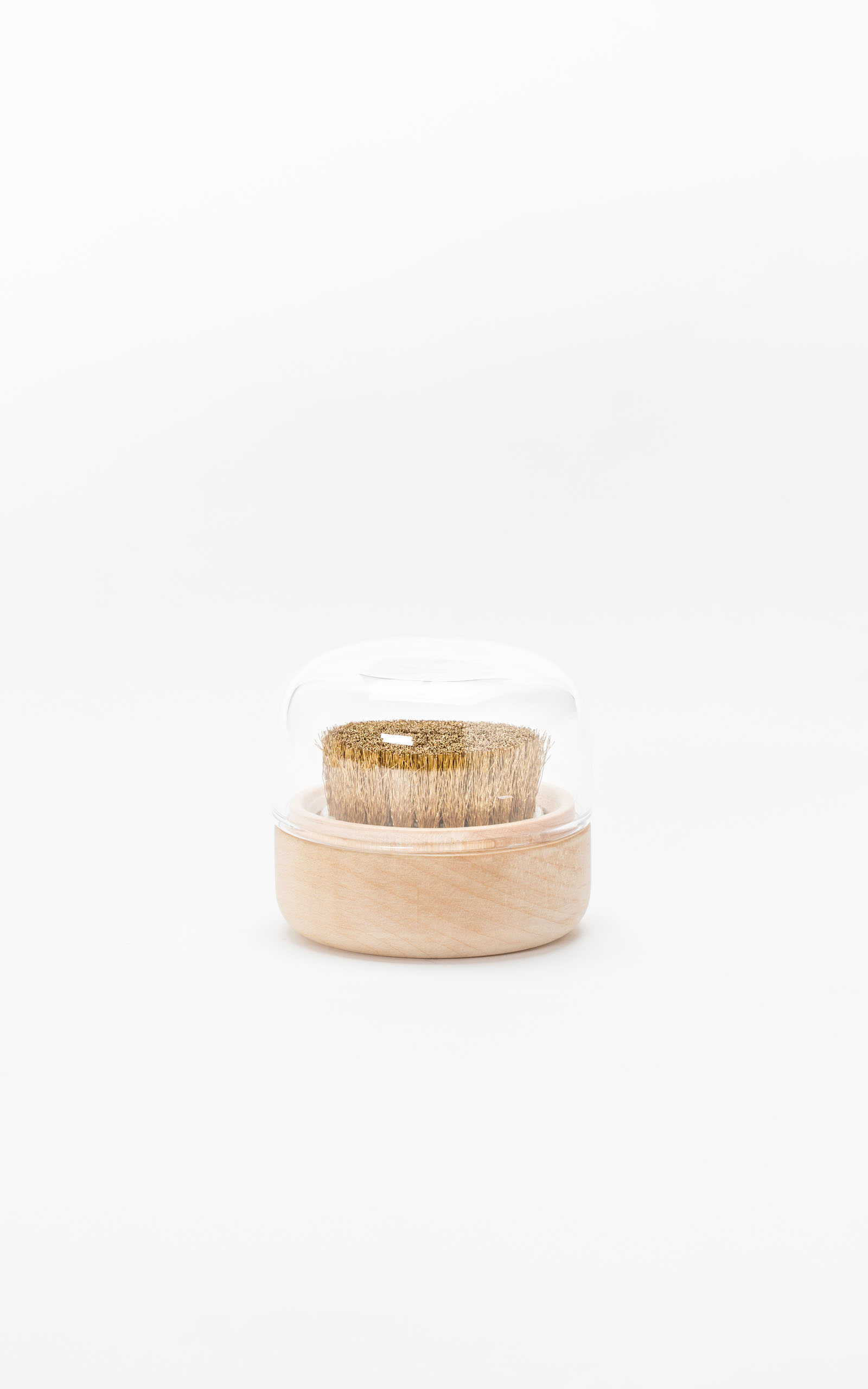 A clothing brush with a minimalistic glass top in front of a white backdrop.