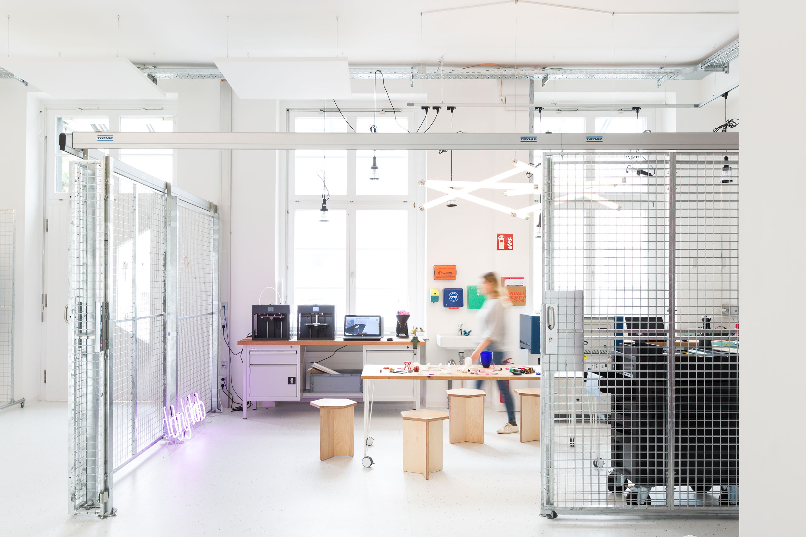 The interior of a lab working space with a person walking through.