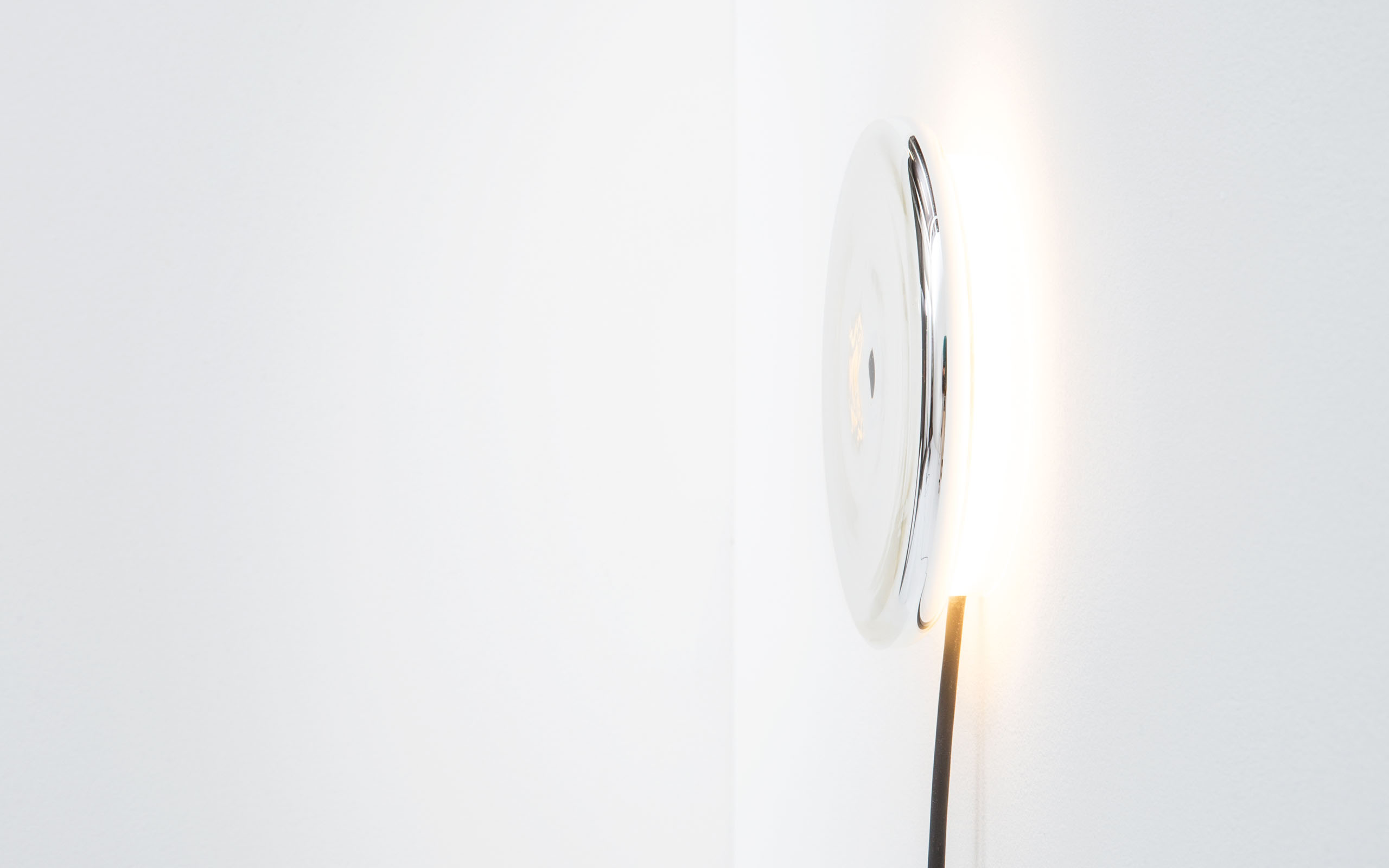A wall light is shown from the side. The body of the light, a silver plated disc reflects the light emitted behind it.