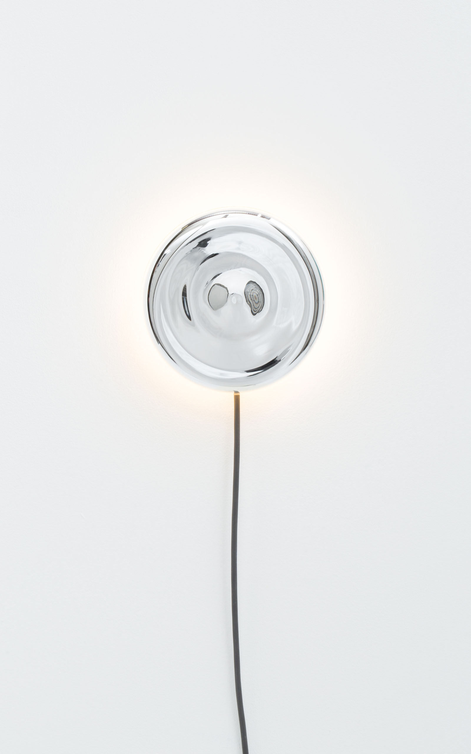 A wall mounted light that consists of a silver plated mirror disc with the light emitting from behind.