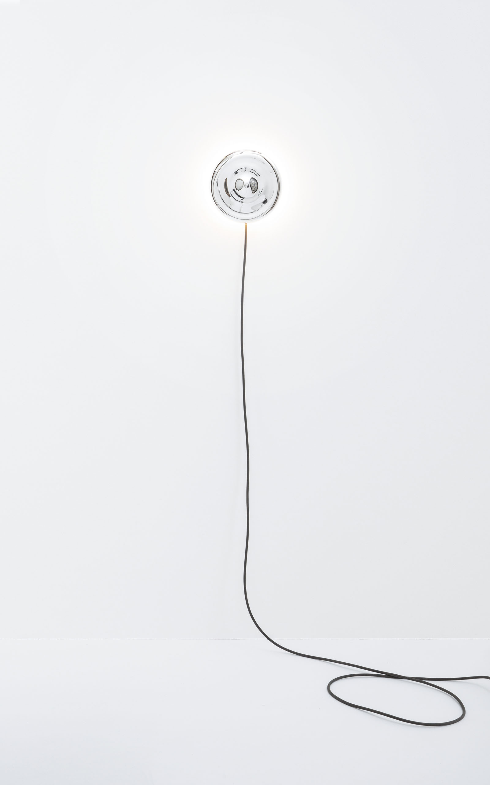 The mirrored body of the wall light is hanging from the wall with the cable starting to curl on the floor.