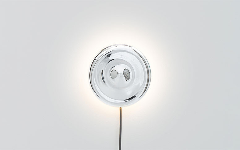 A wall mounted light that consists of a mirror disc and the cable hanging down.