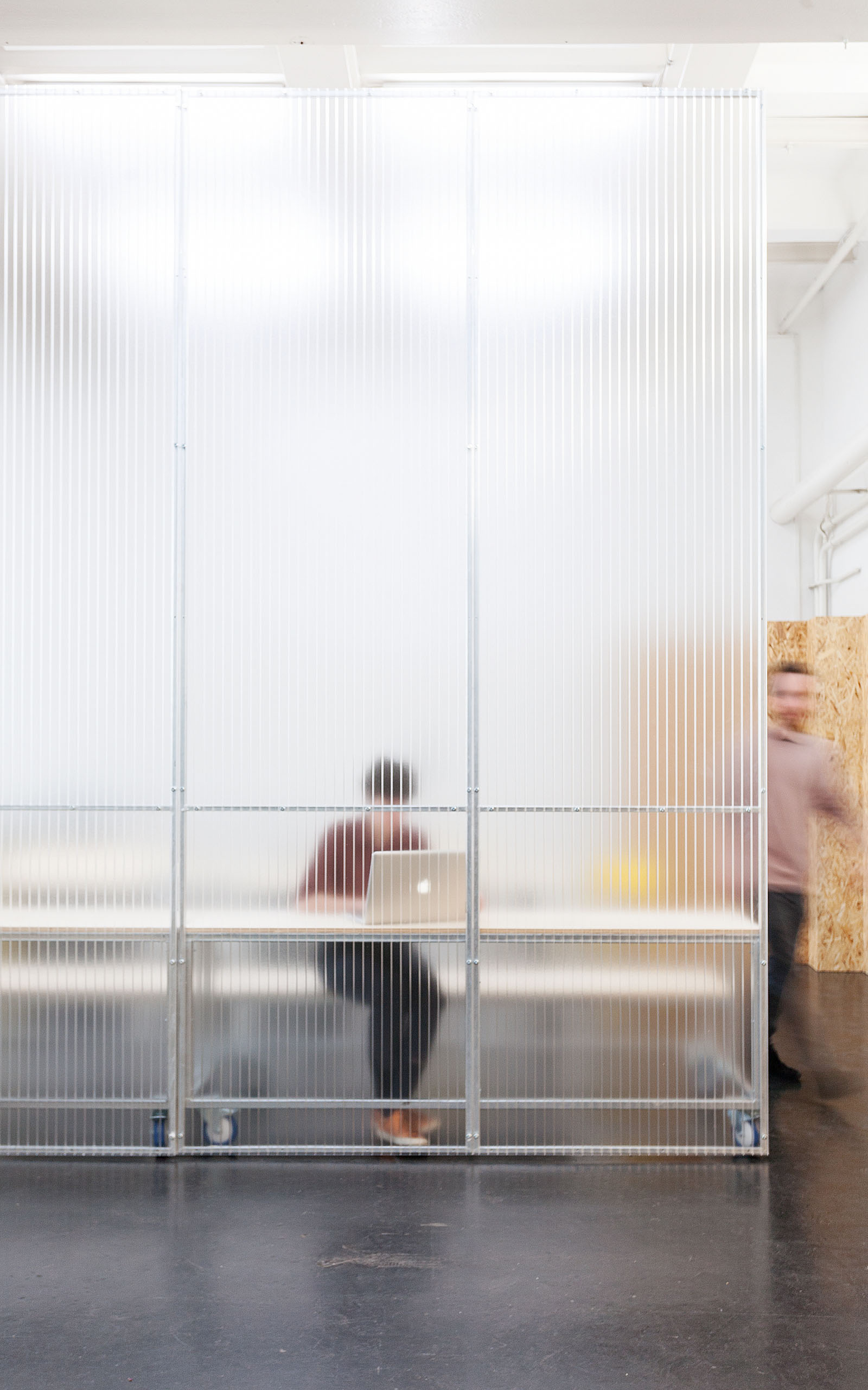 A mobile room divider structure made of translucent material shows the silhouette of a person behind it.