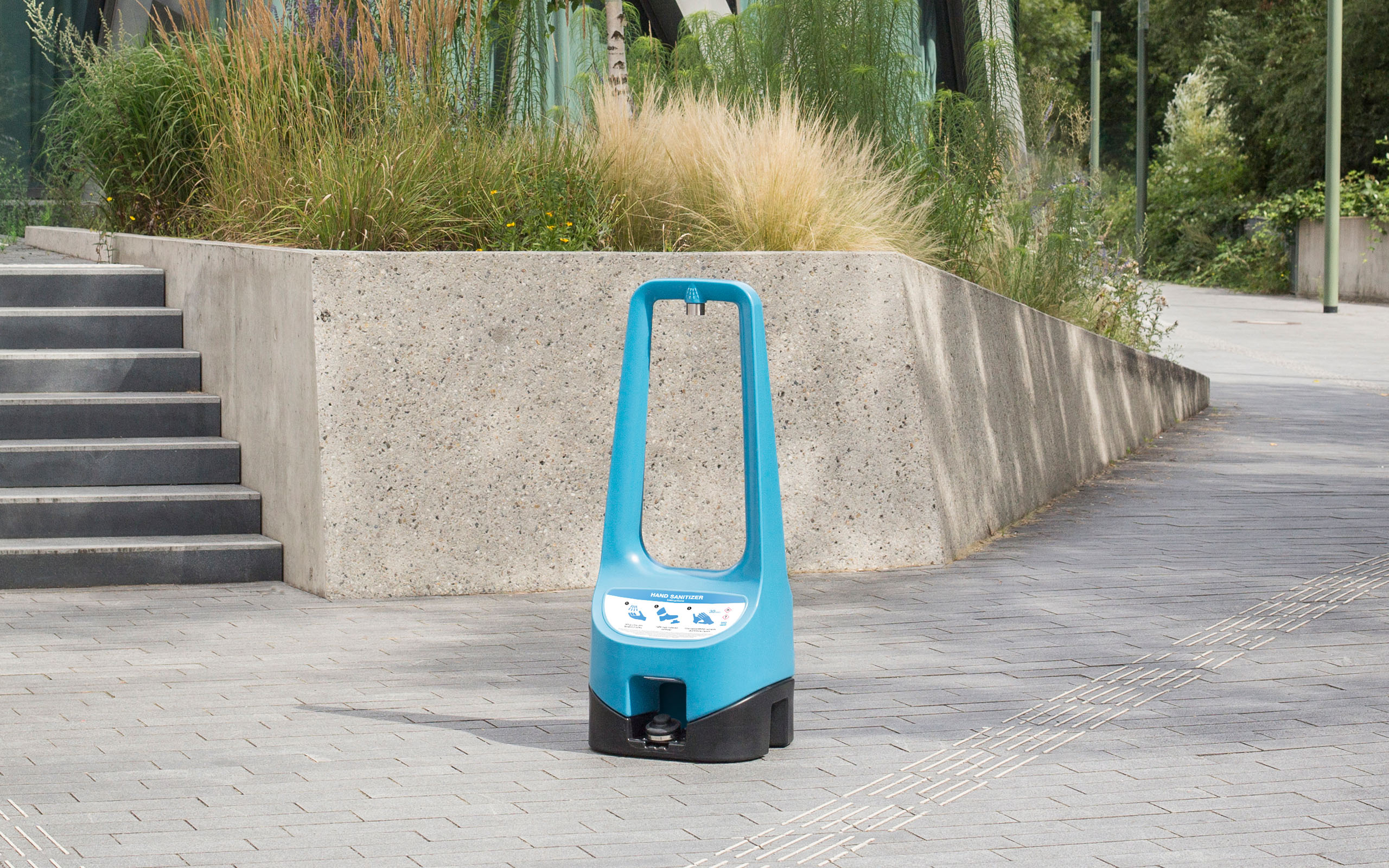 A Toi Care blue hand sanitizer with a foot pump for handling standing outdoors.