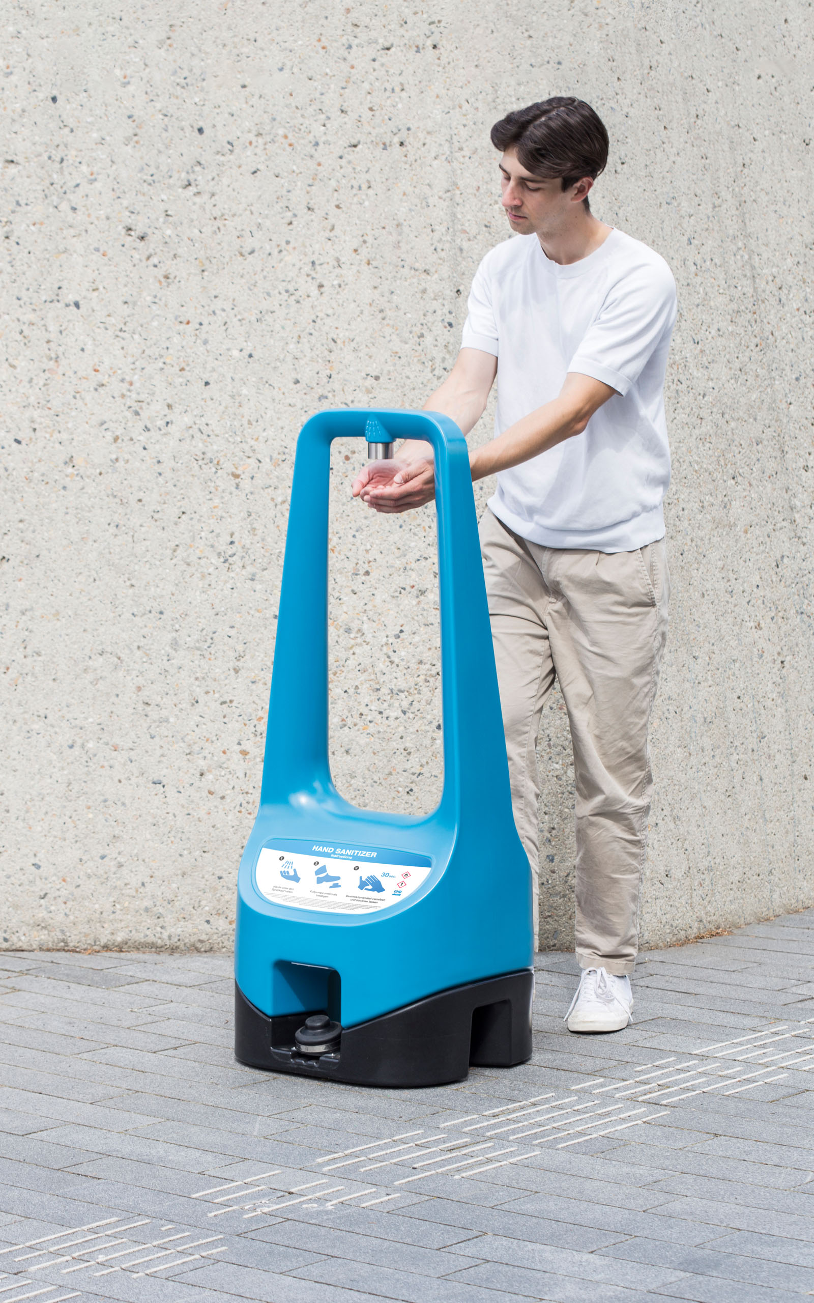 A person shown from the front is using a foot pump to enable a Toi Care hand sanitizer standing outdoors.
