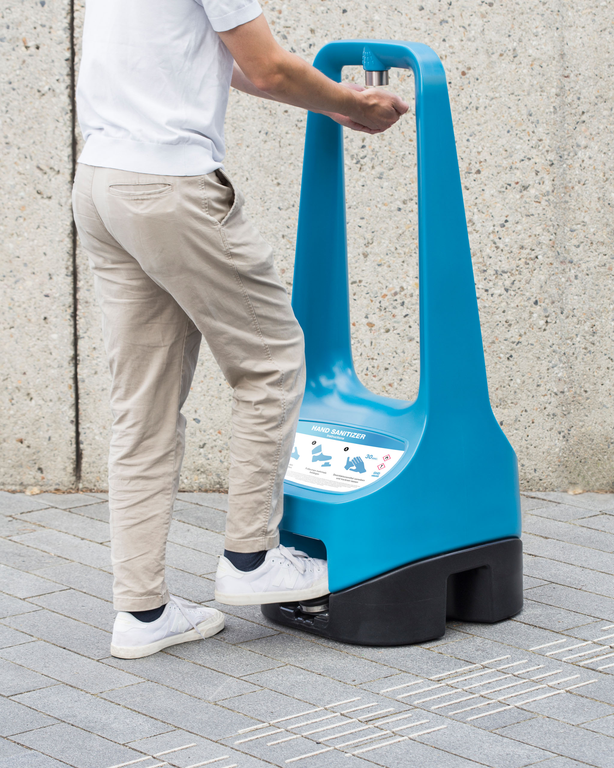 A person is using a foot pump to enable a Toi Care hand sanitizer standing outdoors.